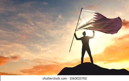 Qatar flag being waved by a man celebrating success at the top of a mountain. 3D Rendering