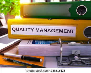 Quality Management - Yellow Office Folder on Background of Working Table with Stationery and Laptop. Quality Management Business Concept on Blurred Background. Quality Management Toned Image. 3D.