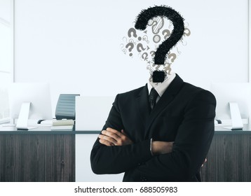 Question mark headed businessman with folded arms in modern office interior. Enquiry and FAQ concept