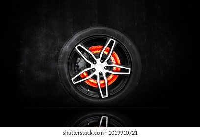 Racing wheel and disc brake scratch burning on black cement wall background. Automotive parts concept. 3D rendering.