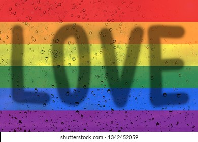 Rainbow flag on background with raindrops and inscription love. LGBT community concept.