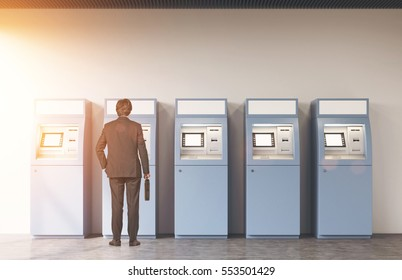 Rear view of a man in a suit holding a suitcase and standing near a row of blue ATM machines in an empty hall. 3d rendering. Mock up. Toned image