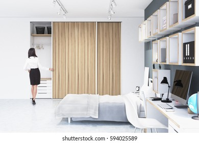 Rear view of a woman standing near a built in wooden wadrobe in a room with a double bed and a number of bookshelves on the wall. 3d rendering, mock up