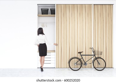 Rear view of a woman standing near a built in wooden wadrobe in a room with hangers and boxes, a set of drawers is in the lower part. There is a bike standing beside it. 3d rendering, mock up