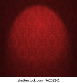 Red damask wallpaper illuminated from a spotlight.