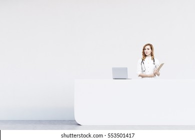 Red haired woman receptionist standing at a counter in a hospital. There is a white wall behind her and a laptop on the desk. 3d rendering. Mock up