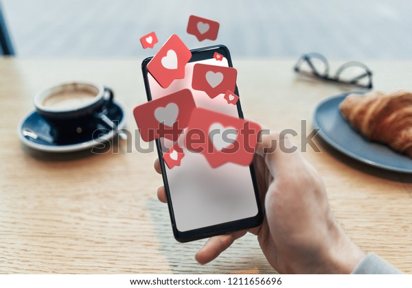 Red heart Like symbols on blank mobile phone screen. Close up of man hand holding mobile phone in cafe. 3d rendering. Social media concept.