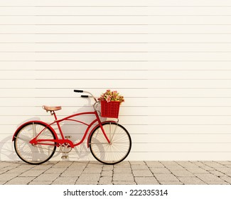 red retro bicycle with basket and flowers in front of the white wall, background