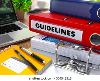 Red Ring Binder with Inscription Guidelines on Background of Working Table with Office Supplies, Laptop, Reports. Toned Illustration. Business Concept on Blurred Background.