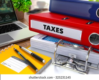 Red Ring Binder with Inscription Taxes on Background of Working Table with Office Supplies, Laptop, Reports. Toned Illustration. Business Concept on Blurred Background.