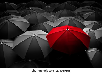 Red umbrella stand out from the crowd of many black and white umbrellas. Business, leader concept, being different concepts