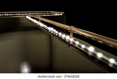A regular empty stripper stage with a bronze railing and a strip of lights on a dark background