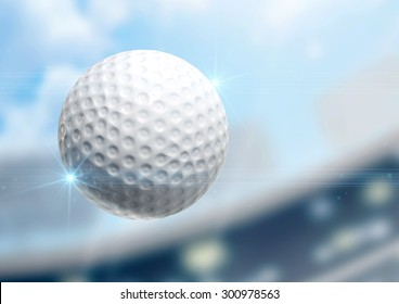 A regular golf ball flying through the air on a stadium background during the daytime
