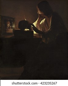 The Repentant Magdalen, by Georges de La Tour, c. 1635-40, French painting, oil on canvas. Candle light silhouettes Mary's left hand which rests on a skull and is reflected in the mirror. Both the sk