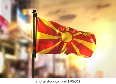 Republic of Macedonia Flag Against City Blurred Background At Sunrise Backlight 3D Rendering