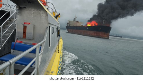 A rescue boat heads towards a fuel ship on fire.