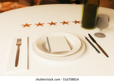 Restaurant rating concept. Dining table with wine, cutlery, spiral notepad and five stars. 3D Rendering