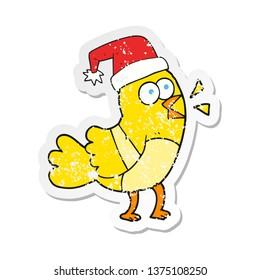 retro distressed sticker of a cartoon bird wearing christmas hat