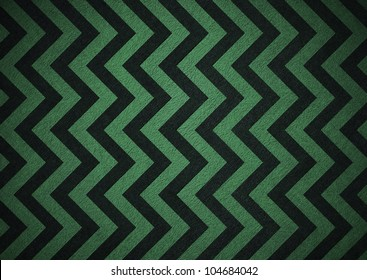 Retro green background of black zigzag chevron stripes, background is patterned wallpaper and vintage grunge background texture design, old abstract background paper for brochure, colorful background