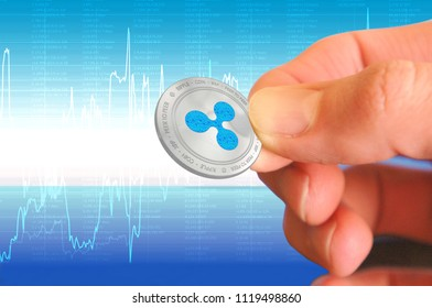 Ripple crypto currency (XRP) closeup. Blue and silver coin in hand. Cyber money.