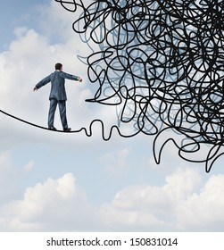 Risk confusion business concept as a businessman on a high wire tight rope walking towards a tangled mess as a metaphor or symbol of overcoming adversity in strategy and finding leadership solutions.