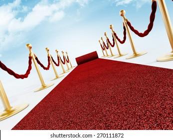 Rolled red carpet and velvet ropes against the blue sky