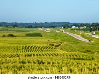 Rolling farmland with fields of corn (maize) along a stretch of U.S. Highway 20 in western Iowa, USA, on a summer morning, with digital oil-painting effect