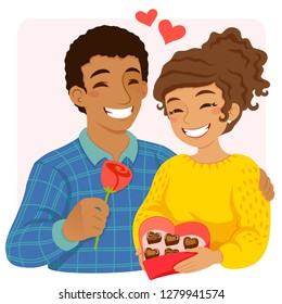 Romantic couple on Valentine's Day, giving each other flowers and heart shaped chocolates.