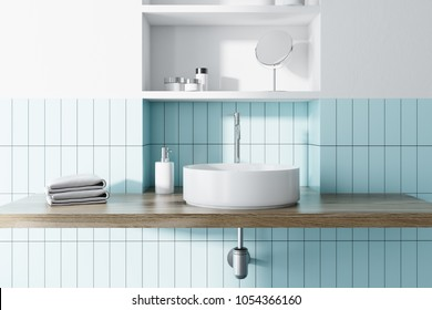 Round sink in a blue tiled and white bathroom interior with wide toiletry shelves behind it. 3d rendering mock up