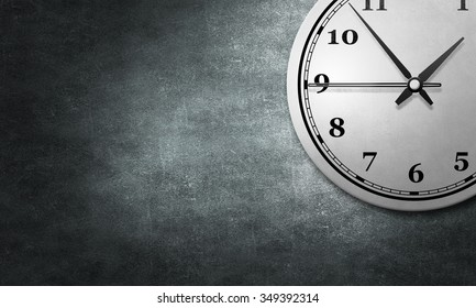 Round wall clock hanging on grey concrete wall
