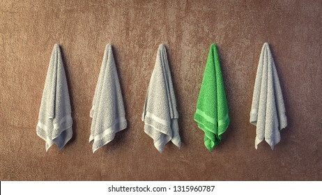 Row of similar grey terry aqua bath towels hanging on wall with one differs with its green color. 3D rendered concept of uniqueness and personalisation