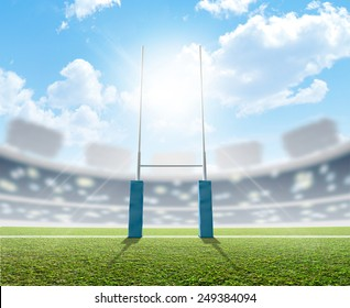A rugby stadium with rugby posts on a marked green grass pitch in the daytime under a blue sky