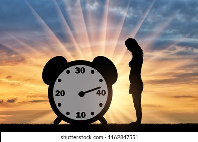 Sad woman standing at the clock hand which shows almost 40 years. Conceptual image of impending menopause in women