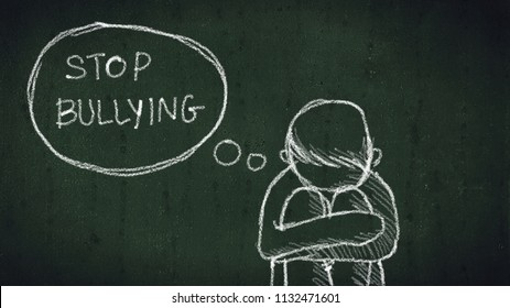 sad young boy sitting on the floor with text stop bullying written with chalk on chalkboard. social problems of humanity