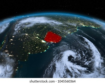 Satellite night view of Uruguay highlighted in red on planet Earth with clouds. 3D illustration. Elements of this image furnished by NASA.