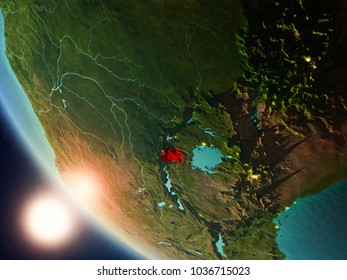 Satellite view of Rwanda highlighted in red on planet Earth with visible country borders during sunset. 3D illustration. Elements of this image furnished by NASA.