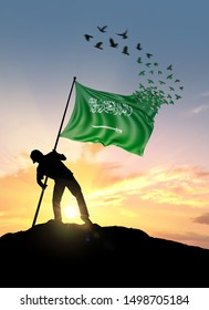 Saudi Arabia flag turn to birds while being planted by a man on a hill during sunrise.