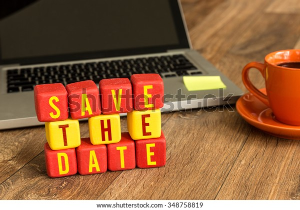 Save the Date on a wood cube in a corporate background