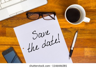 Save the date - written on white paper, lying on desk with glasses, laptop, mobile phone, coffee in office