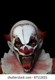 Scary crazed clown with blood dripping from his mouth.  Isolated on a black background.