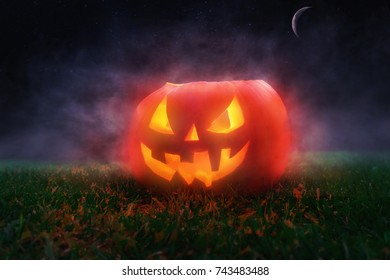 Scary halloween background with real pumpkin, smoke and moon. Halloween concept.