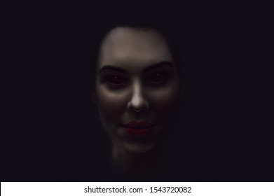 Scary and sexy vampire woman face with black eyes  and bloody red lips in the dark.  Diabolic  and possessed by evil spirit young girl. Halloween look. Dead demonic female in darkness.
