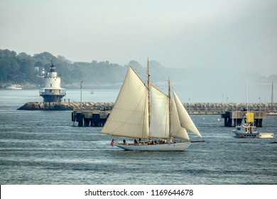 Schooner sailing past Portland Breakwater Light, also called Bug Light, built in 1875, in South Portland, Maine, USA, with digital oil-painting effect, for vintage, nautical, and tourism themes
