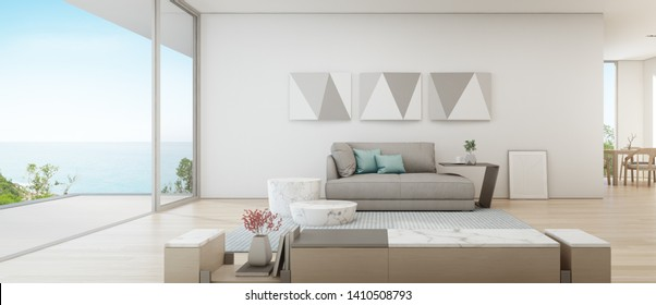 Sea view dining and living room of luxury summer beach house with large glass door near wooden terrace. TV stand against gray sofa in vacation home or holiday villa. Hotel interior 3d illustration.