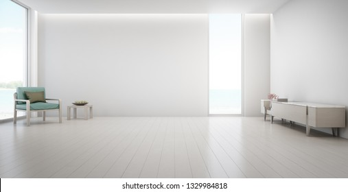 Sea view large living room of luxury summer beach house with TV stand and wooden cabinet. Empty white concrete wall background in vacation home or holiday villa. Hotel interior 3d illustration.