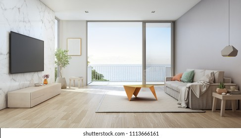 Sea view living room of luxury beach house with glass door and wooden terrace. TV on white marble wall against sofa near indoor plant in vacation home or holiday villa. Hotel interior 3d illustration.