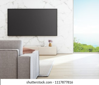 Sea view living room of luxury beach house with glass window and wooden floor. TV on white marble wall against sofa in vacation home or holiday villa. Hotel interior 3d illustration.