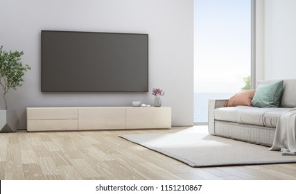 Sea view living room of luxury beach house with glass window and wooden floor. TV on white wall near sofa in vacation home or holiday villa. Hotel interior 3d illustration.