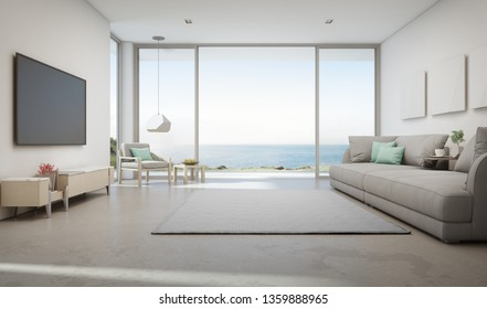 Sea view living room of luxury summer beach house with large glass door and wooden terrace. TV on white wall against big gray sofa in vacation home or holiday villa. Hotel interior 3d illustration.