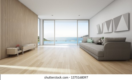 Sea view living room of luxury summer beach house with swimming pool and wooden terrace. TV stand against big gray sofa in vacation home or holiday villa. Hotel interior 3d illustration.